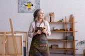 středního věku umělec v zástěře drží štětec u stojanu