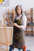 středního věku umělec v zástěře drží štětec při malování doma