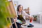 zralá žena drží štětec a paletu, zatímco dosahují červené barvy v trubici a sedí v blízkosti plátna