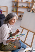 joyful middle aged woman holding paintbrush and palette with colorful paints near blank canvas
