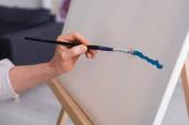 kivágott kilátás középkorú nő gazdaság ecset festés közben vászon