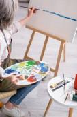 zralá žena drží paletu a štětec a malování na plátně