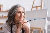 šťastný malíř středního věku s šedými vlasy drží štětec při pohledu pryč