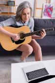 Frau mittleren Alters mit grauen Haaren lernt Akustikgitarre neben Laptop mit leerem Bildschirm auf Couchtisch zu spielen