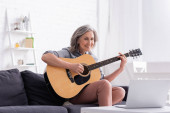 happy middle aged woman learning to play acoustic guitar near laptop on coffee table