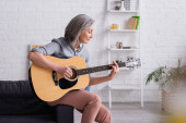 mature woman with grey hair playing acoustic guitar in living room