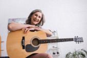 veselá zralá žena s šedými vlasy drží akustickou kytaru a směje se v obývacím pokoji