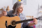 zralá žena s šedými vlasy drží smartphone a zároveň se učí hrát na akustickou kytaru