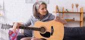 mature woman with grey hair looking at smartphone while learning to play acoustic guitar, banner