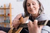 pozitivní zralé ženy s šedými vlasy hrát akustickou kytaru na rozmazané popředí
