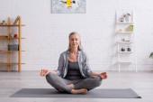 érett nő szürke haj ül lótuszban pózol jóga mat