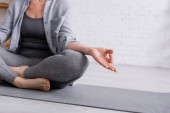 részleges érett nő ül lótuszban póz jóga mat