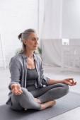 reife Frau mit grauen Haaren sitzt in Lotus-Pose und meditiert auf Yogamatte