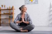 glückliche reife Frau mit grauen Haaren sitzt mit betenden Händen in Lotus-Pose auf Yogamatte