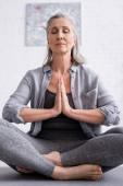 reife Frau mit betenden Händen und geschlossenen Augen sitzt in Lotus-Pose auf Yogamatte