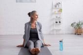 šťastný zralý žena s šedými vlasy sedí na podložce jógy v blízkosti sportovní láhve