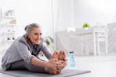 fröhliche reife Frau mit grauen Haaren dehnt sich auf Yogamatte neben Sportflasche