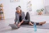 usmívající se dospělá žena sedící na podložce jógy při sledování výukového programu na notebooku