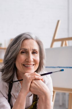 Joyful middle aged painter with grey hair holding paintbrush stock vector