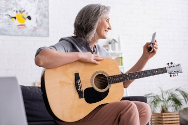 Smiling mature woman with grey hair holding smartphone while learning to play acoustic guitar stock vector