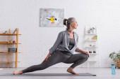 boční pohled na flexibilní ženu středního věku cvičící jógu na podložce