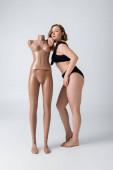 teljes hossza túlsúlyos és mezítlábas nő fürdőruhában támaszkodó műanyag próbababa fehér