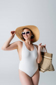 overweight and joyful woman in sunglasses and swimsuit holding bag while adjusting straw hat isolated on white