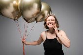 happy plus size woman in black slip dress and crown holding golden balloons on grey