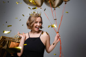 happy plus size woman in slip dress and crown holding balloons and shopping bags near confetti on grey