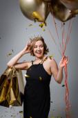 boldog plusz méret nő csúszás ruha és korona tartó arany léggömbök és bevásárló táskák közelében konfetti szürke