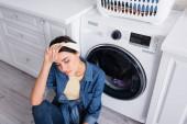 Blick von oben auf erschöpfte Hausfrau, die neben Waschmaschine in Küche sitzt