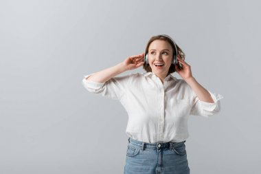 excited plus size woman in wireless headphones listening music isolated on grey