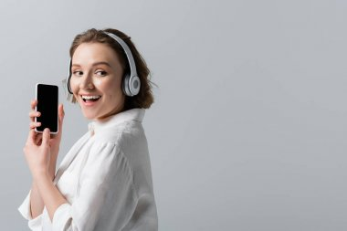 happy plus size woman in wireless headphones listening music and holding smartphone with blank screen isolated on grey