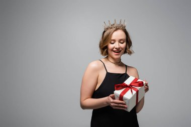 Excited plus size woman in slip dress and crown holding present isolated on grey stock vector