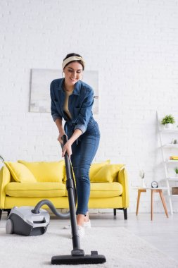 Smiling housewife cleaning carpet with vacuum cleaner in living room stock vector