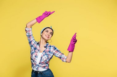 Cheerful young housewife in rubber gloves pointing with fingers isolated on yellow stock vector