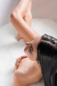 pohled na smyslnou ženu pokrývající prsa při koupeli v mléce