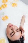 mladá žena se zavřenýma očima dotýkající se obličeje při relaxaci v mléčné lázni s citrusy