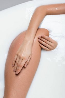 Cropped view of woman touching hip while enjoying milk bath stock vector