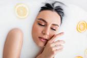 pohled na mladou ženu, jak se koupe v mléce s čerstvými plátky citrusů
