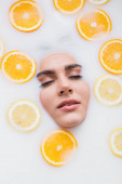 felső kilátás a női arc a tejben fürdő szeletelt citrom és narancs