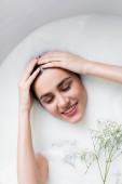 usmívající se žena dotýkající se vlasů při koupání v mléce s gypsophila květy