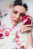 junge Frau hält Rose, während sie Milchbad mit Blütenblättern nimmt