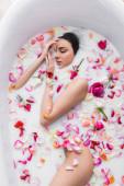vrchní pohled na krásnou ženu relaxující v mléčné koupeli s okvětními lístky růží