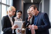 Geschäftsleute mit Papiermappe und Smartphone blicken auf verschwommenes digitales Tablet