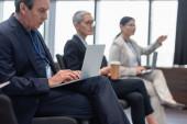 Starší podnikatel pomocí notebooku v konferenční místnosti