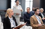 Geschäftsfrau hält Papiermappe neben verschwommenen Kollegen im Konferenzraum