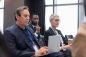 African american businessman looking away during seminar near colleagues