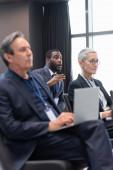 Afrikanischer Geschäftsmann spricht im Konferenzraum mit verschwommenen Kollegen