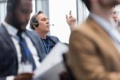 Reifer Geschäftsmann in Headset-Gespräch während Business-Konferenz